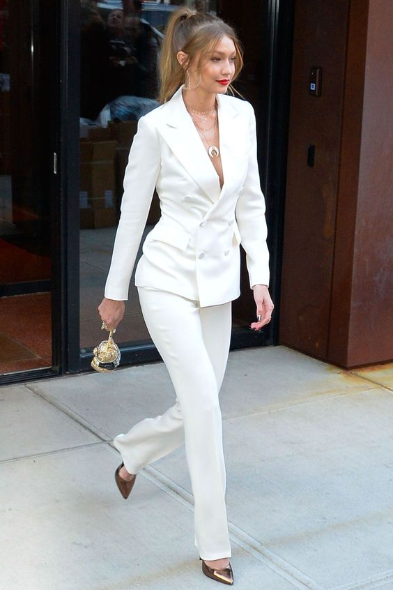 a white pantsuit with a long double-breasted blazer, copper shoes and layered necklaces for a modern look