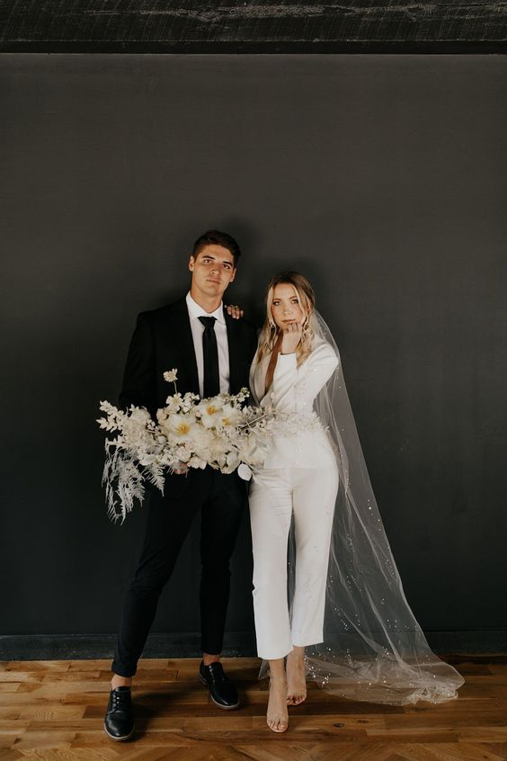 a white pantsuit with cropped pants and a blazer, tan shoes and a long embellished veil for a modern bride