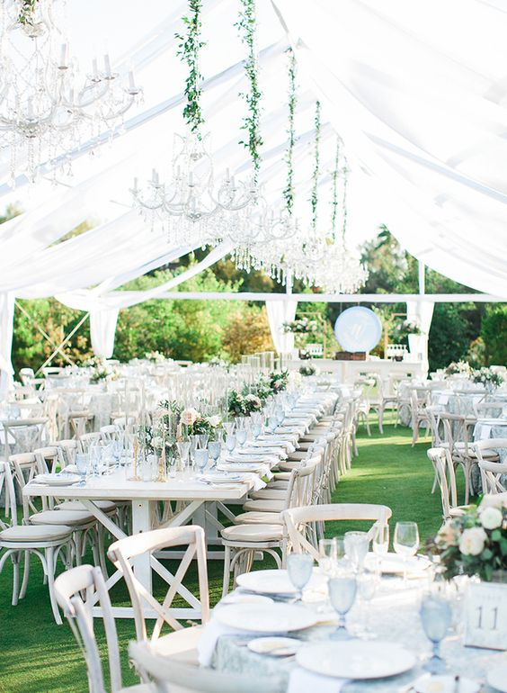 an all-white spring wedding reception with greenery, pastel blooms and white chandeliers on greenery ropes