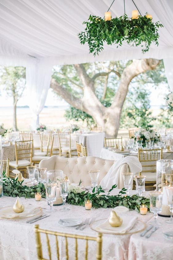 an elegant white spring wedding reception with greenery chandeliers, greenery runners, candles and gold pears
