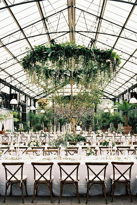 an indoor spring wedding reception with greenery chandeliers, greenery arrangements, trees in pots and candles