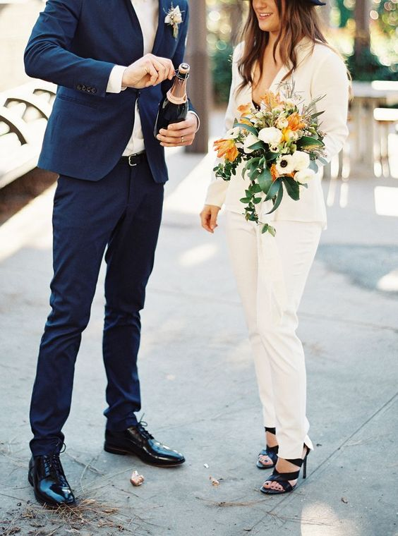 an ivory pantsuit with a deep V neckline and black heels and a black bra to compose a chic modern bridal look