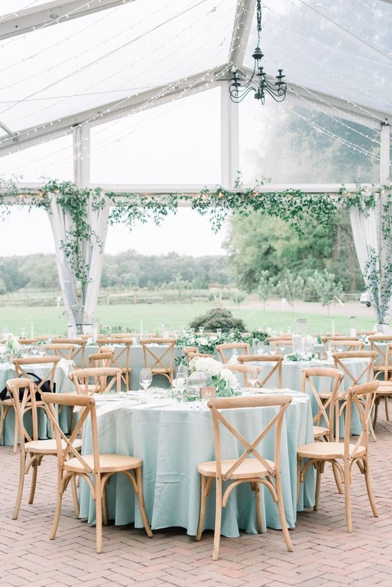 an outdoor-indoor spring wedding reception with pastel blue linens, white floral arrangements and greenery