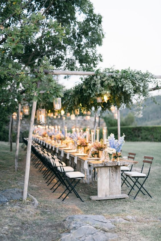 an outdoor spring wedding reception with candle lanterns, greenery and pastel blooms
