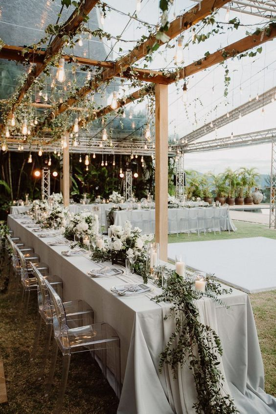 an outdoor spring wedding reception with greenery and bulbs on the beams, white blooms and candles and greenery runners