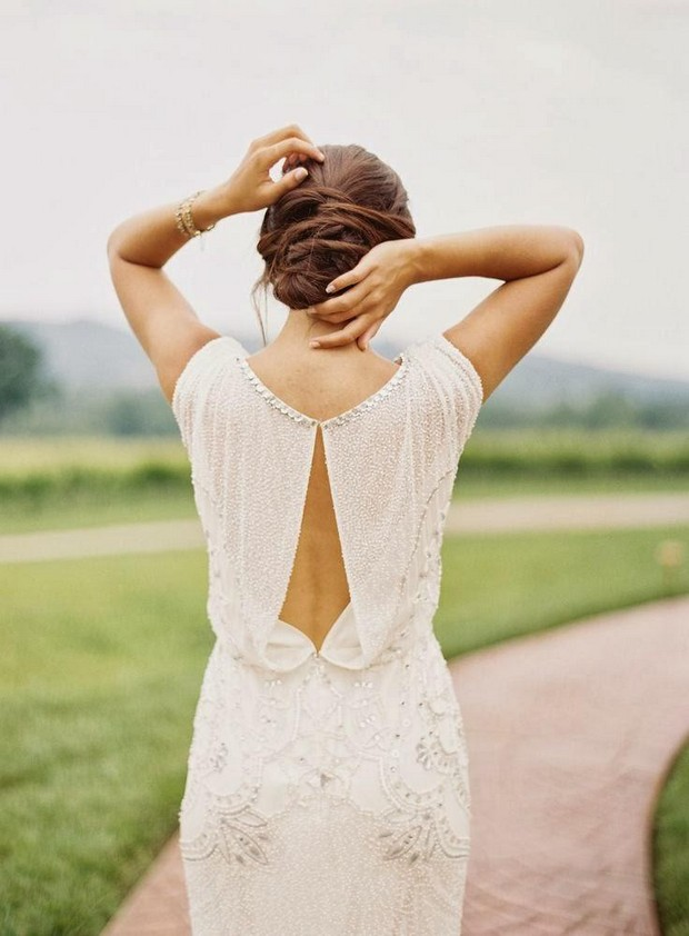 a beautiful fitting embellished wedding dress with a cutout on the back that delicately shows off the back itself