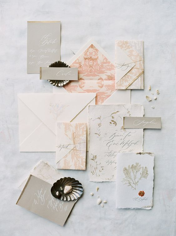 a beautiful neutral and pastel wedding invitation suit with a raw edge, muted color prints and seashells
