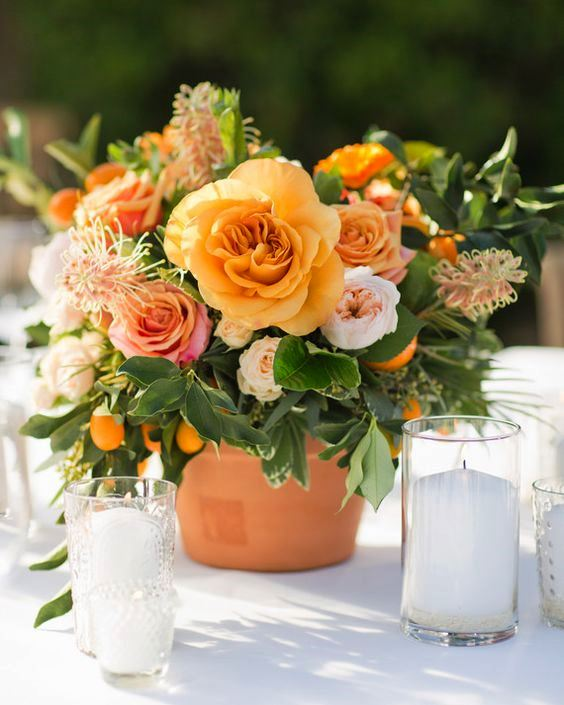 a beautiful summer wedding centerpiece of peachy, yellow and rust-colored blooms, foliage and kumquats