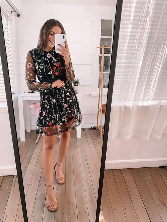 a black mini A-line dress with bright floral embroidery, nude heels and illusion long sleeves for a fall or winter wedding