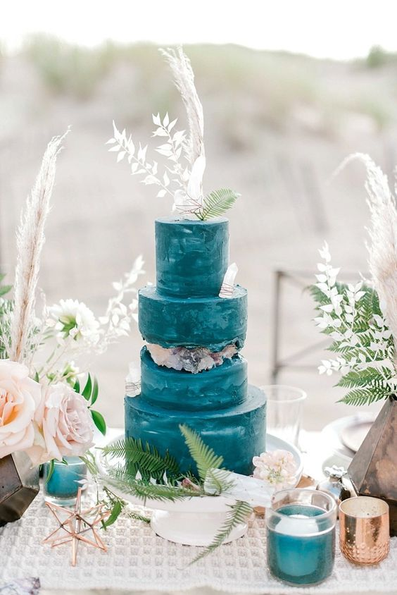 a bold blue beach wedding cake accented with crystals, leaves and dried herbs is lovely and bright