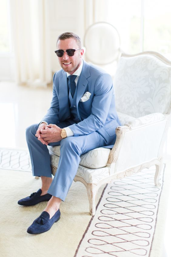 a bold blue three piece suit with a white shirt, a navy tie and navy moccasins and no socks