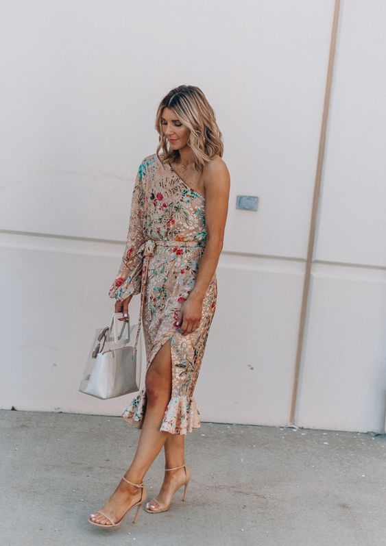 a bold floral one shoulder midi dress with a slit and a long sleeves plus statement earrings for a summer wedding