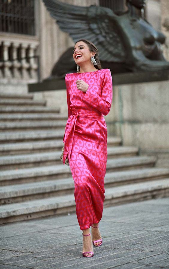 a bold pink printed maxi dress with a high neckline and accented shoulders, a sash and pink strappy shoes plus statement earrings