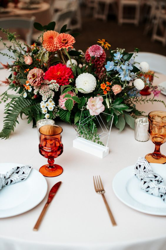 a bold summer wedding centerpiece of textural greenery, red, rust and white and blue blooms
