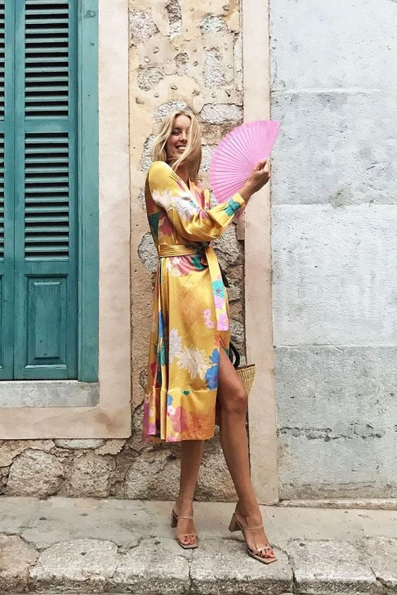a bold yellow silk midi wrap dress with bright floral prints, nude square toe shoes for a bright summer wedding