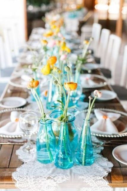 a bright and simple cluster wedding centerpiece of blue bottles and yellow blooms is lovely and stylish