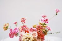 a bright dimensional summer wedding centerpiece of a white vase, fuchsia, pink and peachy blooms looks refined and bold