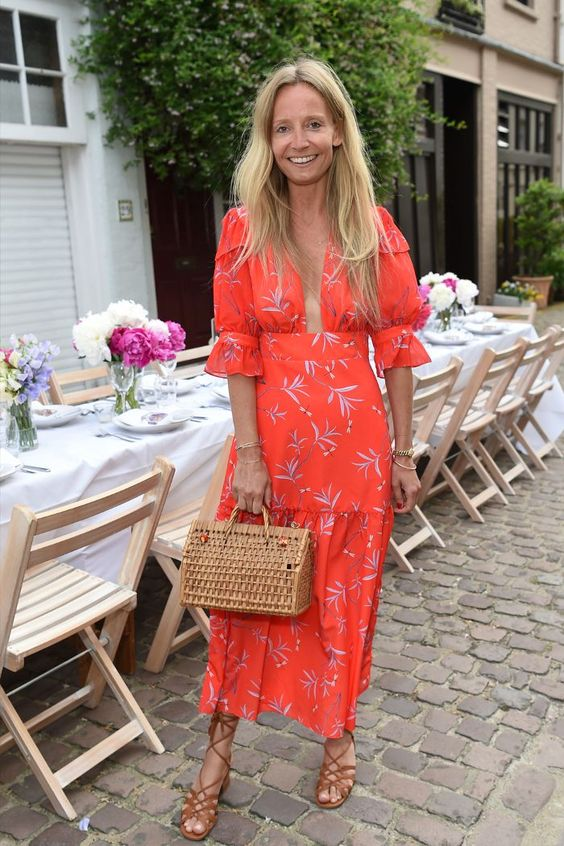 a bright red floral midi dress with puff sleeves, brown strappy shoes, a basket bag for a bright summer wedding