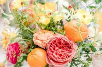 a bright summer wedding centerpiece in a bucket – pink, fuchsia, yellow and peachy blooms, oranges and greenery