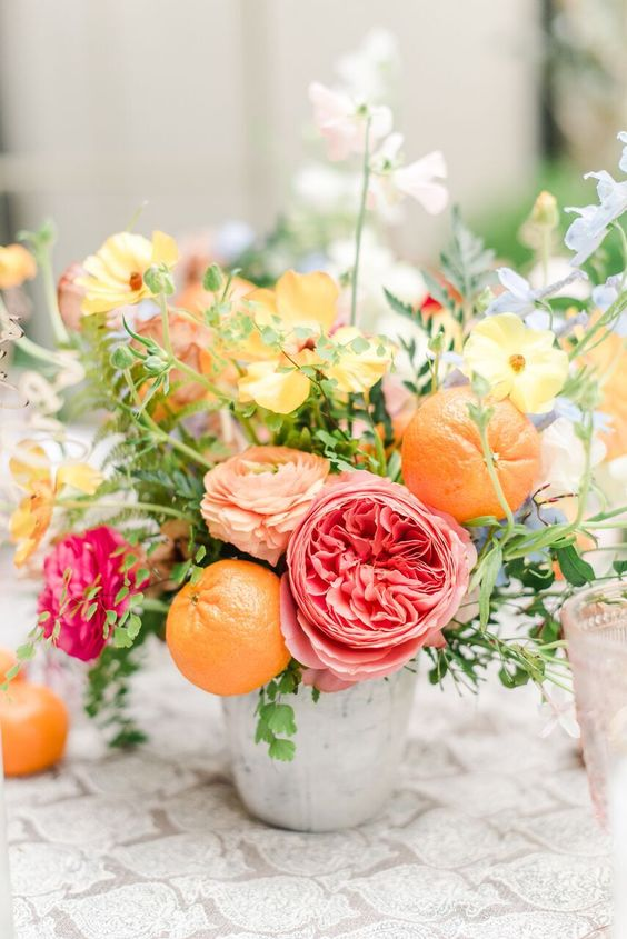a bright summer wedding centerpiece in a bucket   pink, fuchsia, yellow and peachy blooms, oranges and greenery