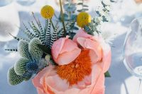 a bright summer wedding centerpiece of billy balls, a pink peonies, thistles, cacti and eucalyptus