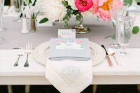 a bright summer wedding centerpiece of light and hot pink bloom and white ones, and texturla greenery is wow