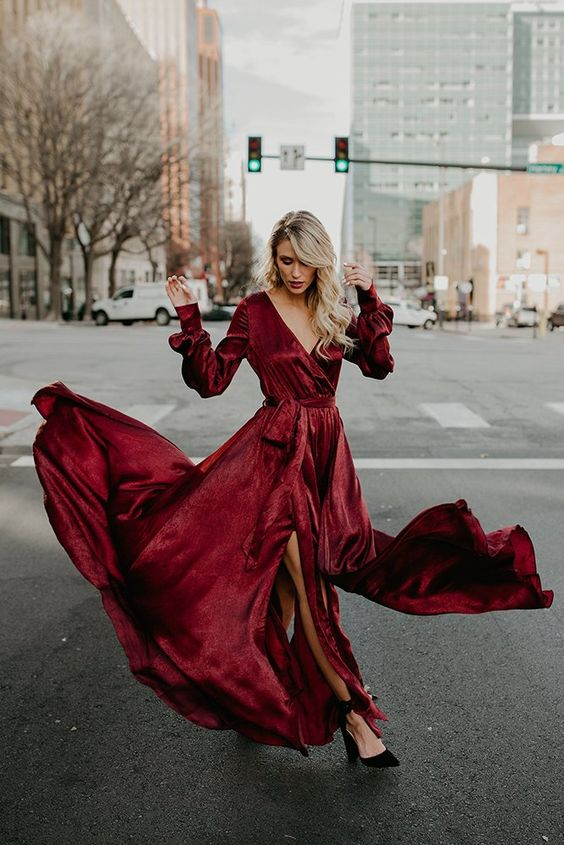 a burgundy wrap maxi dress with a deep neckline, long sleeves and a slit, blakc ankle strap heels for a fall or winter wedding