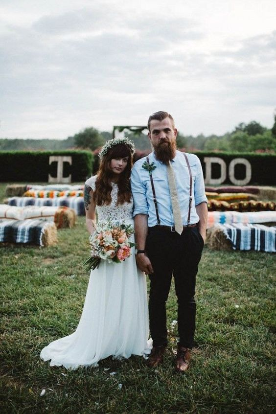 a casual groom's look with a blue shirt, thin leather suspenders, black pants and brown shoes plus a creamy tie