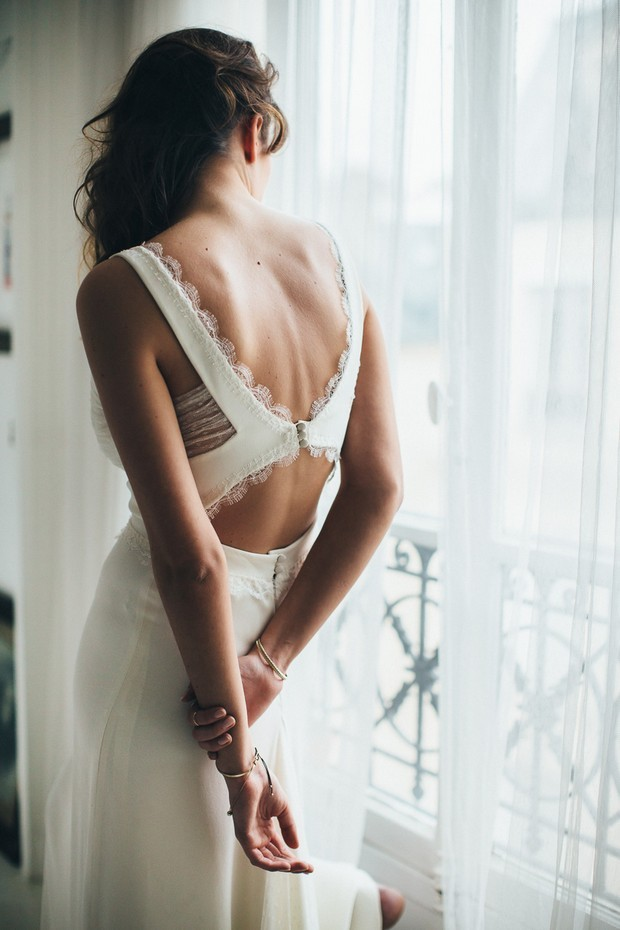 a charming modern fitting wedding dress with a veyr catchy back - a cutout one with buttons and lace edges is dreamy