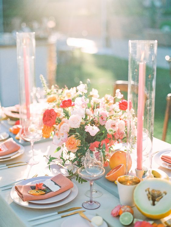 a cheerful summer wedding centerpiece of light pink, red, orange blooms and greenery and pink candles