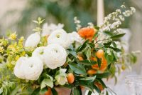a chic and bold summer wedding centerpiece of white, orange and yellow blooms and kumquats looks wow