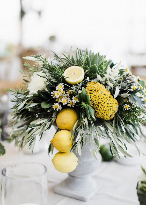 a chic summer wedding centerpiece of white and yellow blooms, daisies and lemons hanging down