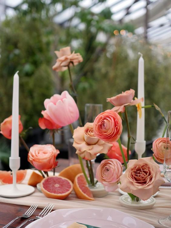 a cluster wedding centerpiece of coral, pink and peachy blooms, citrus and candles in candlesticks is lovely