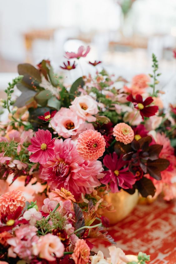 a colorful summer weddign arrangement of ourple, burgundy, pink, orange blooms and foliage is lovely and bold