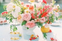 a colorful summer wedding arrangement of pink, orange, peachy, red and blush blooms and some greenery
