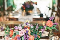 a colorful summer wedding arrangement of purple, red and lilac blooms and foliage is very vibrant