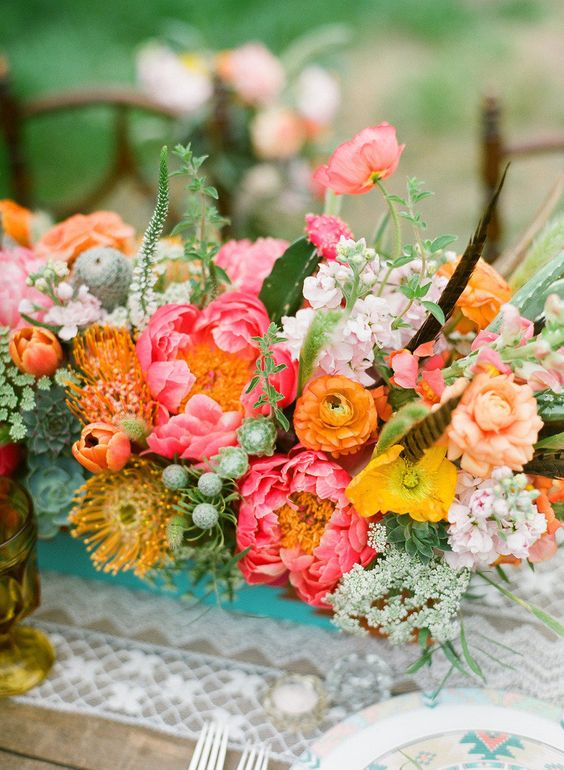 a colorful summer wedding centerpiece of a blue box, fuchsia, orange, yellow blooms, greeneyr, cacti and feathers