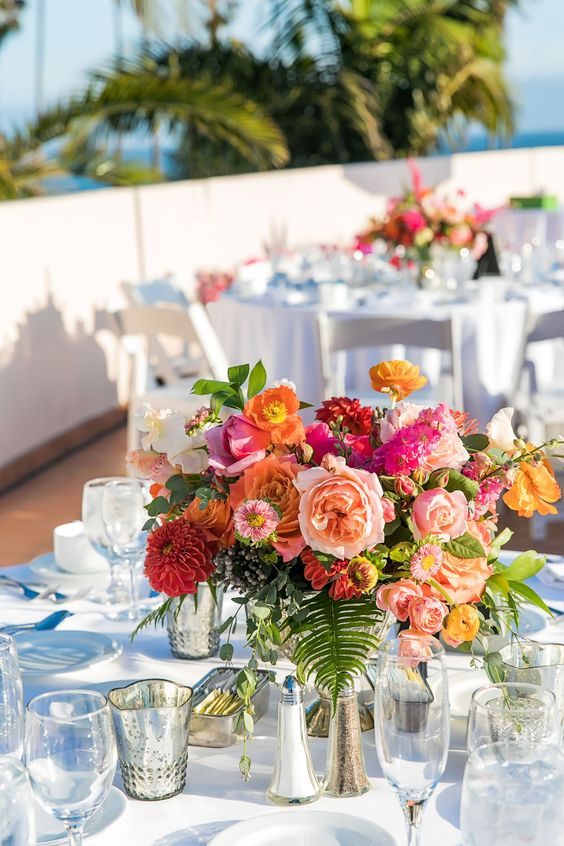 a colorful summer wedding centerpiece of hot pink, orange, light pink, red blooms and foliage is amazing