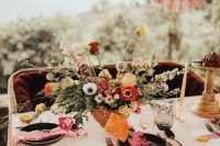 a colorful summer wedding centerpiece of red, yellow, light pink and white blooms and textural greenery
