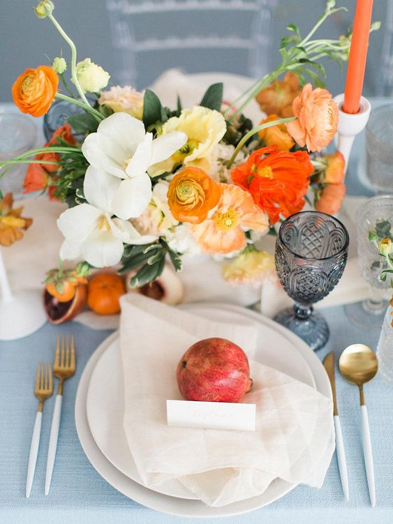 a colorful summer wedding centerpiece of white, orange, rust and red blooms and foliage is gorgeous
