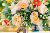 a colorful wedding centerpiece of red, pink, white and peachy blooms and foliage and a wooden table number