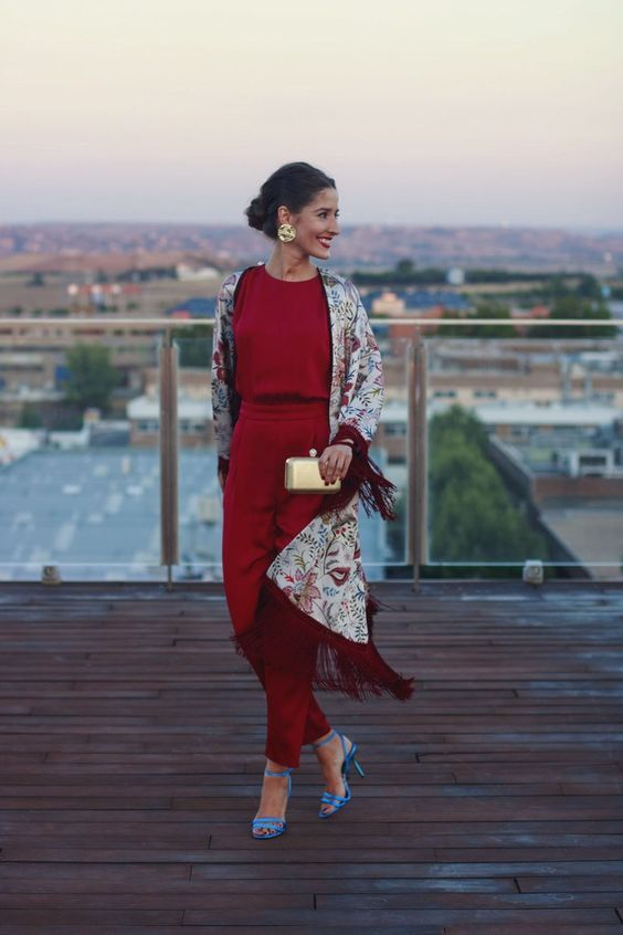 a deep red fitting jumpsuit, a floral fringe kimono, blue shoes, a metallic clutch and matching earrings for the fall
