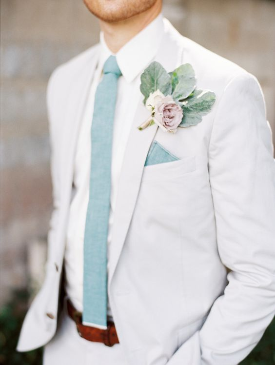 a fresh summer wedding outfit with an off-white suit, a mint blue tie and a pale floral boutonniere