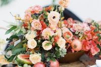 a gorgeous lush wedding centerpiece of peachy, blush and red  blooms, berries, pomegranates and grapes