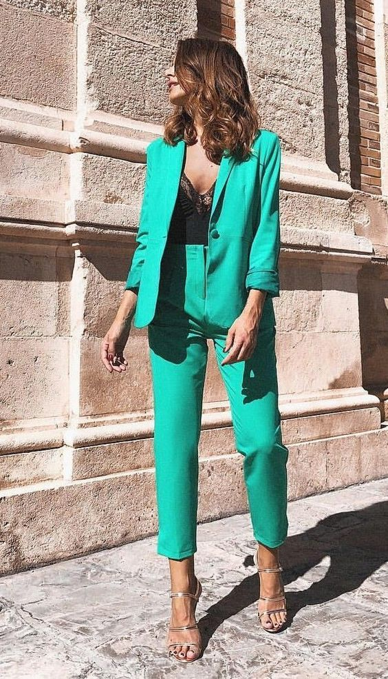 a green pantsuit with an oversized blazer, silver heels and a black lace bodysuit for a refined and chic fall wedding