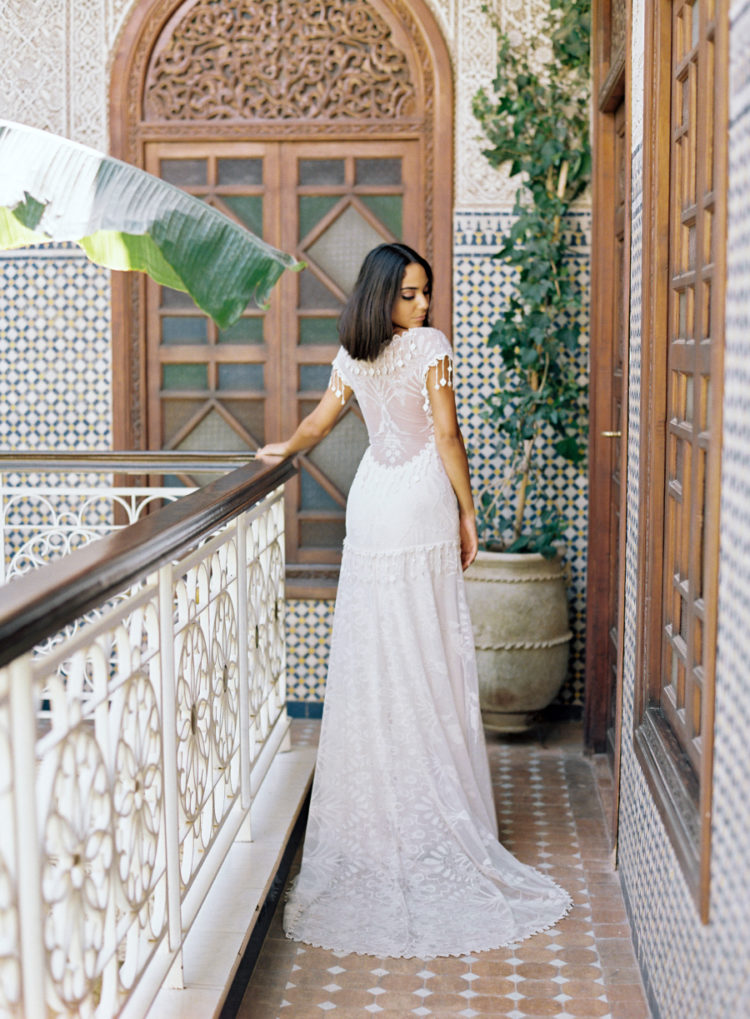 a jaw-dropping A-line boho lace wedding dress with an illusion back with hanging lace pieces is a gorgeous idea for a Moroccan wedding