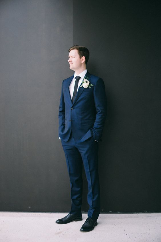a laconic modern groom's look with a navy suit, a white shirt, a black tie and black shoes