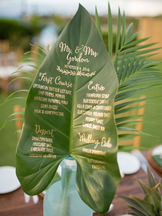 a large leaf with gold calligraphy is a creative and cool wedding menu for a tropical wedding