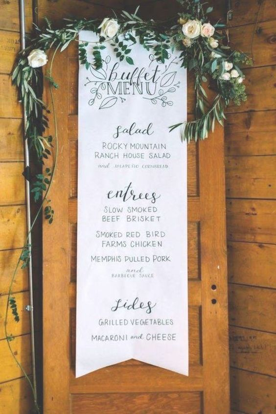 a long paper wedding menu with a greenery and neutral bbloom runner over it for a romantic wedding