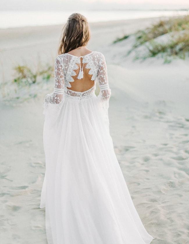 a lovely boho A-line wedding dress with a bodice of boho lace, a pleated plain skirt with a train and tassels on the cutout back